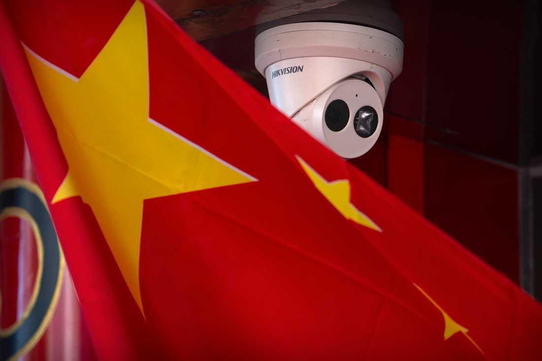 En övervakningskamera nära en kinesisk flagga vid en butik i Kinas huvudstad Peking.