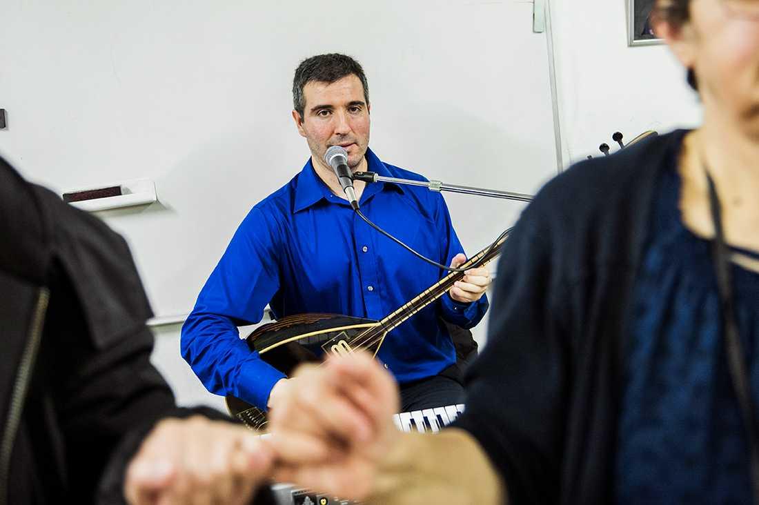 Musikern Ali Yilmaz spelar saz, ett långhalsat lutinstrument.