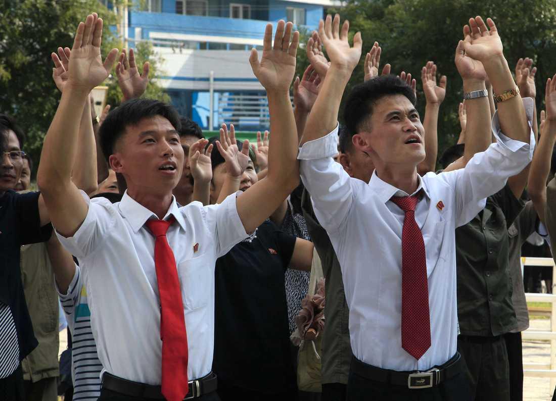 Människor på en gata i Nordkoreas huvudstad Pyongyang reagerar på nyheten om landets provsprängning.