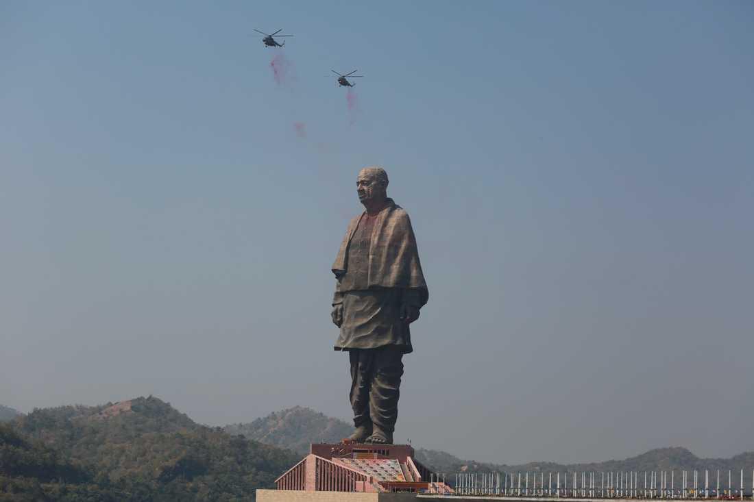 Helikoptrar släpper blommor över statyn under invigningen.