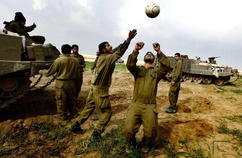Israeliska soldater roar sig med en fotboll under ett uppehåll i striderna strax utanför Gaza.