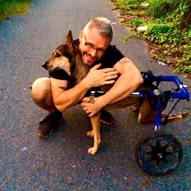 Här är Michael med en av hans egna hundar Coke som han tagit hand om sedan Coke var valp. Coke är förlamad och har därför specialdesignad rullstol.