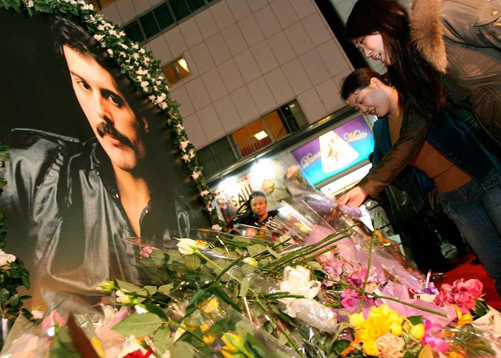 Queen-fans i Tokyo lämnar blommor vid Freddie Mercurys porträtt.