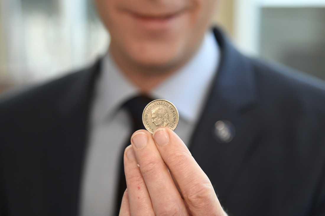 Tobias Billström håller upp myntet.