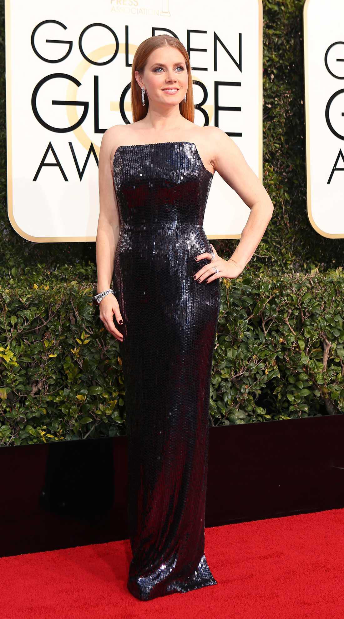 Amy Adams Jag är inte direkt megaförtjust i snittet i den här klänningen även om paljetterna gör att Adams nästan ser ut som en statyett själv. Tom Ford har designat och som alltid blir det elegant, men som sagt toppdelen ser något avhuggen ut.  2 plus