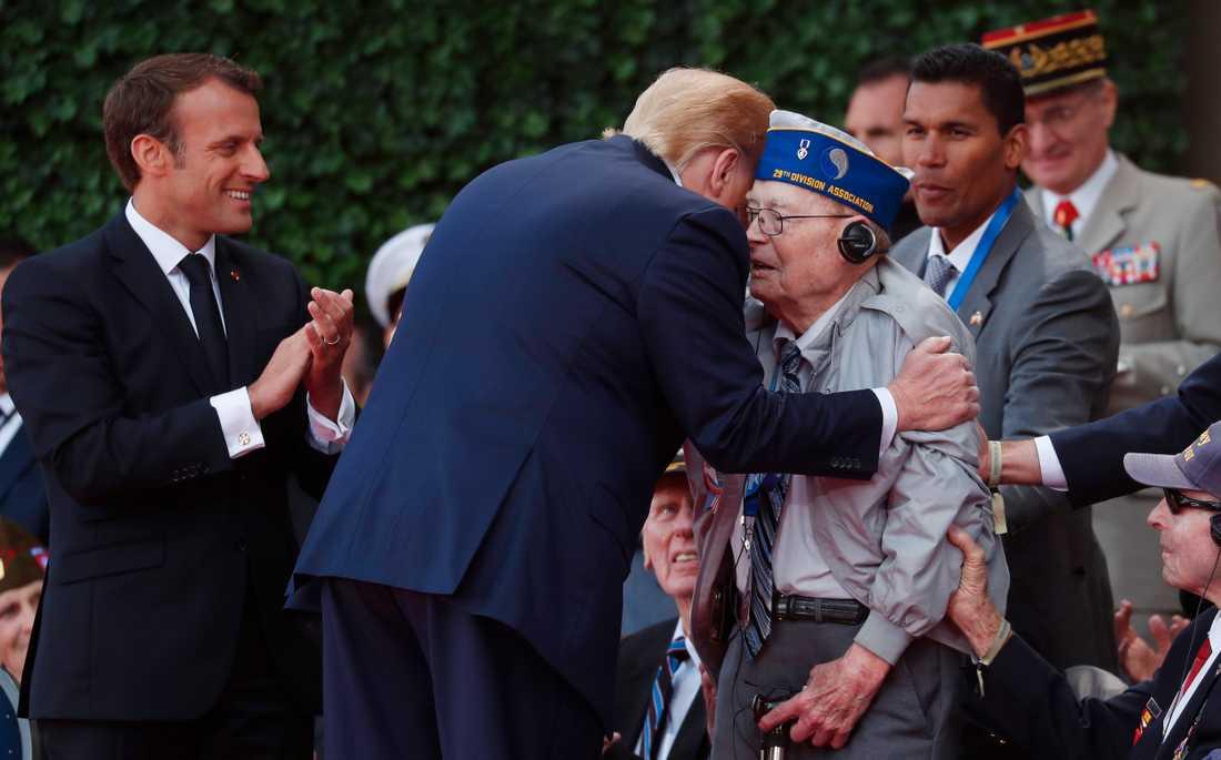 USA:s president Donald Trump omfamnar en av de veteraner som var med under D-dagen och som deltog i 75-årsdagens ceremonier. Frankrikes president Emmanuel Macron står bredvid och applåderar.