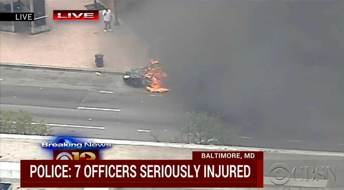 Livebilder visar hur en polisbil satts i brand.