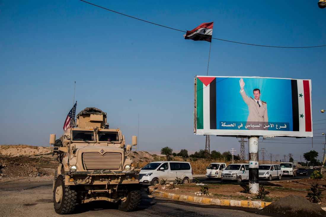 En amerikansk militärkonvoj i staden Qamishli i norra Syrien bredvid en bild av landets president Bashar al-Assad. Arkivbild.