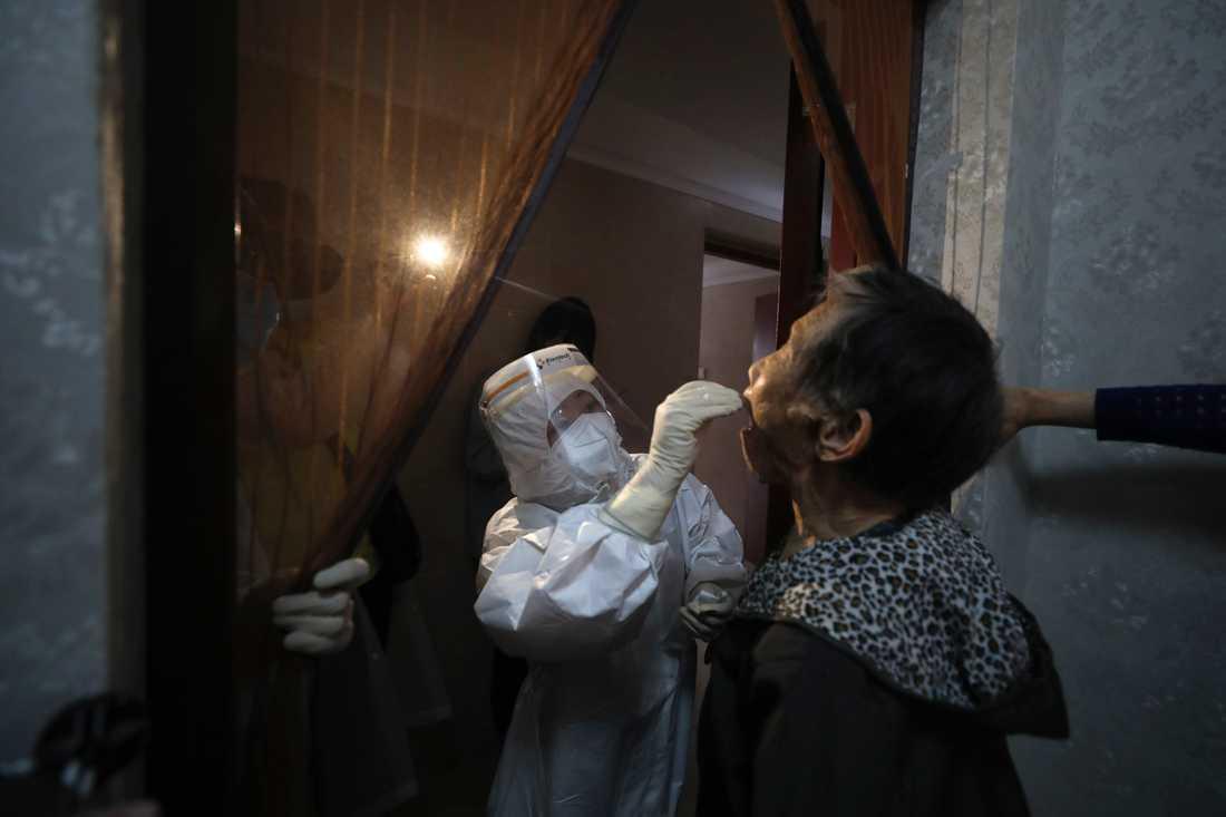 En sjukvårdsarbetare genomför ett hemtest i Wuhan under torsdagen.