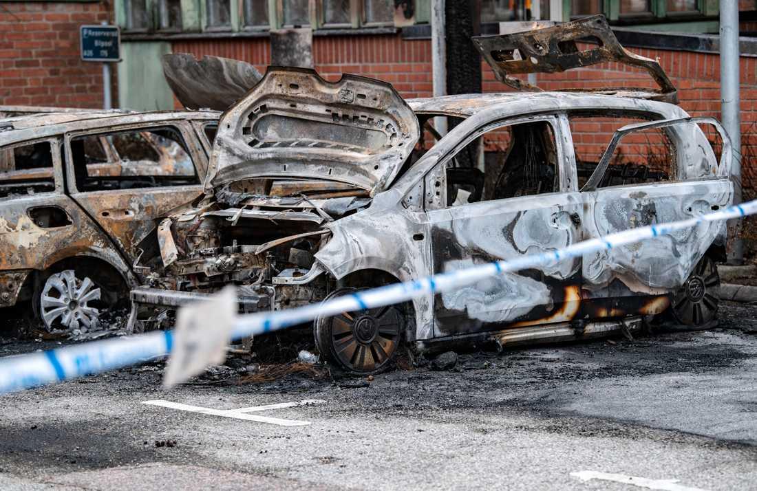 Tre utbrända bilar bakom polisens avspärrningar vid Region Skånes lokaler i september.