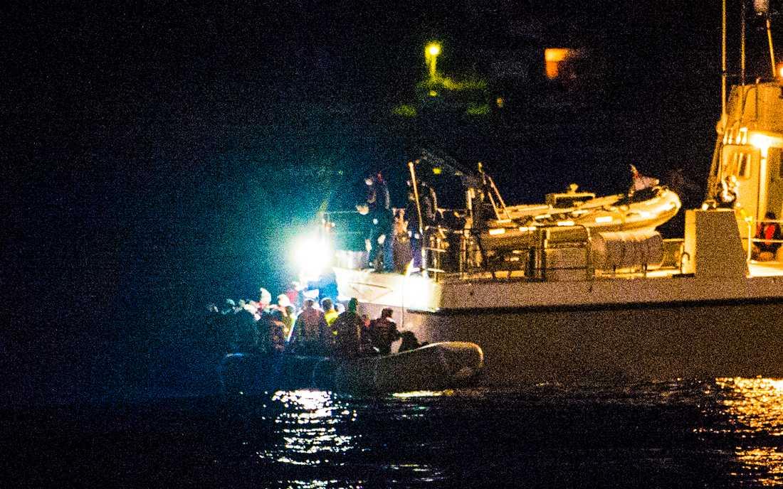 """""""Vi var 520 på båten. 356 drunknade"""". Berättar den unga kvinnan, där hon sitter i sektion B på arbetsförmedlingen, och matas med olika formulär. (Arkivbild. Grekiska kustbevakningen möter upp en flyktingbåt på Medelhavet.)."""