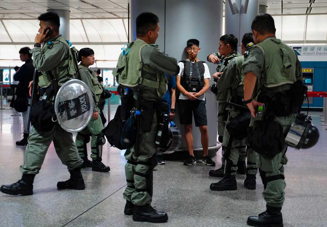 Polis kontrollerar en passagerares bagage.