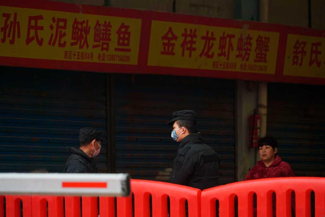 Polis på plats utanför den marknad i storstaden Wuhan där tidiga fall av coronasmittade befunnit sig. Arkivbild.