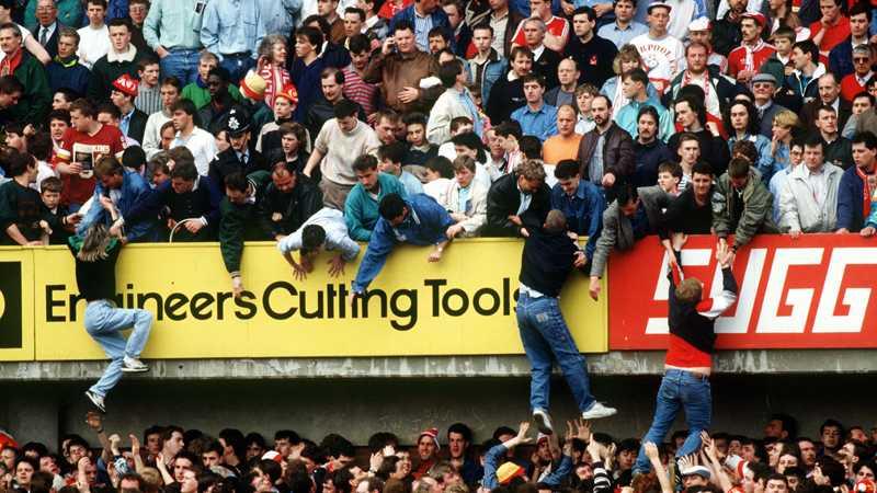 En bild från Hillsborough-katastrofen 1989. Supportrar flyr trängseln och får hjälp av fans på en övre sektion.
