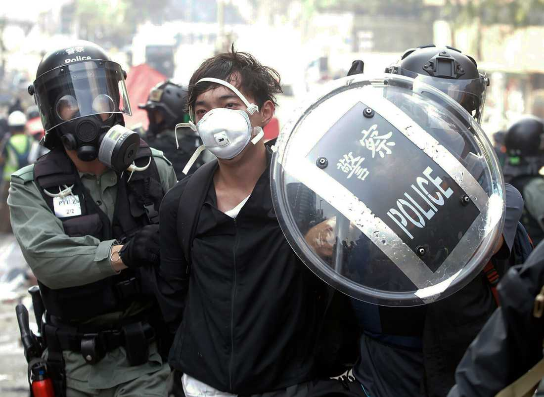 Polisen griper en demonstrant nära Hongkongs polytekniska universitet i Hongkong.