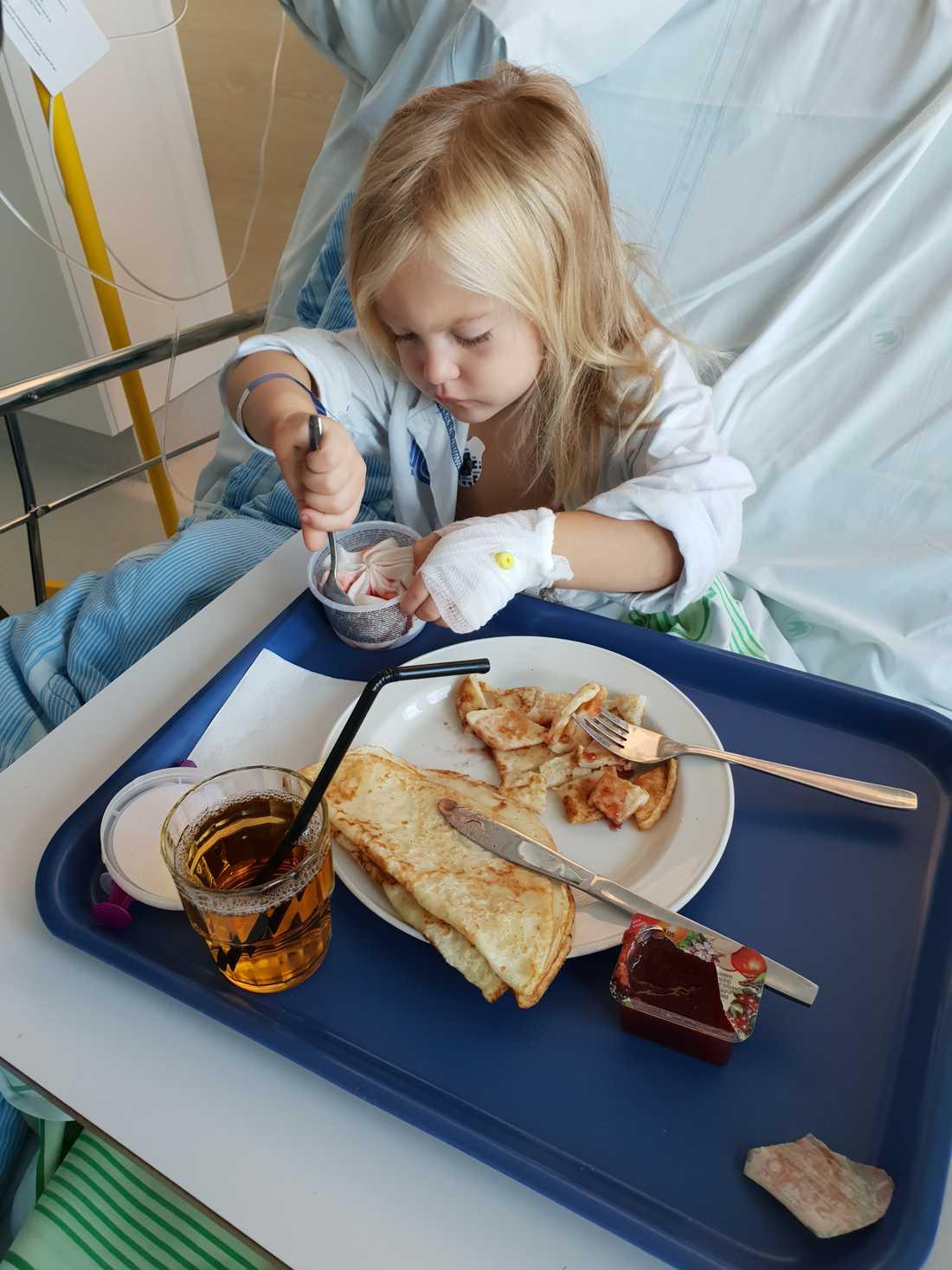 Ellie äter pannkakor i sjukhussängen.