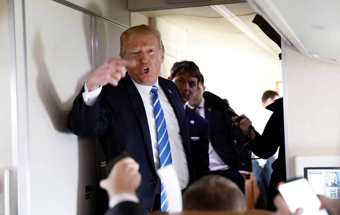 Trump pratar med reportrar ombord på flygplanet Air force one.