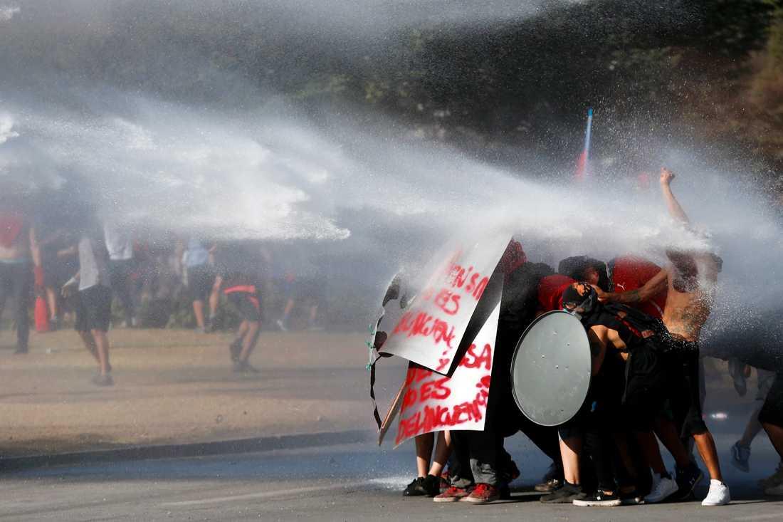 Regimkritiska demonstranter står emot trycket från vattenkanonerna i Chiles huvudstad Santiago den 15 november.