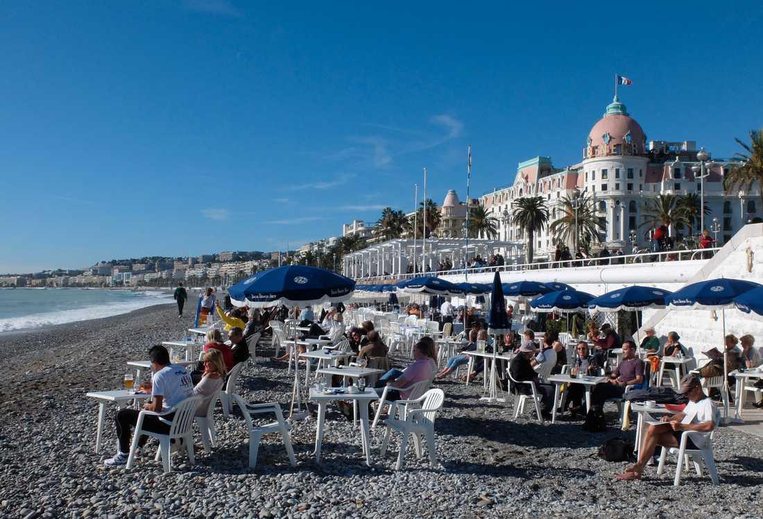 Människor njuter av solen på stranden i Nice på den franska rivieran. Arkivbild.