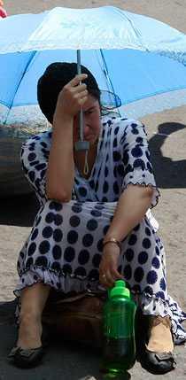 En kvinna på samma busstation, där människor nu tvingas betala chockhöjda biljettpriser.