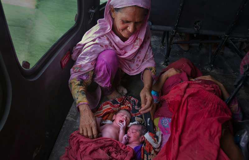 Lycklig mormor Miru Mai, mormor till de båda tvillingarna, ler lyckligt i räddningshelikoptern på väg från katastrofområdet. Barnens mamma Zahida Perveen vilar ut på båren bredvid.