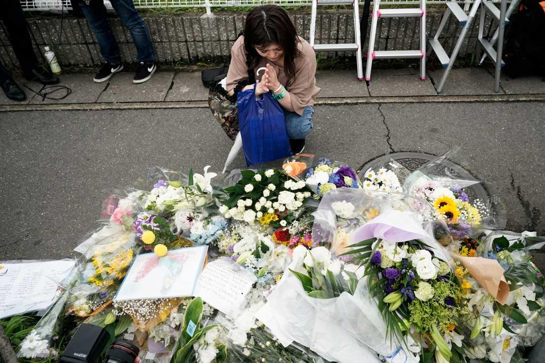 En kvinna ber för offren vid animationsstudion Kyoto Animation dagen efter den förödande branden.