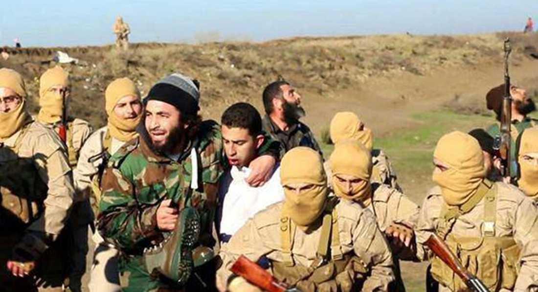Terrorister från IS visar upp den tillfåntatagne soldaten.