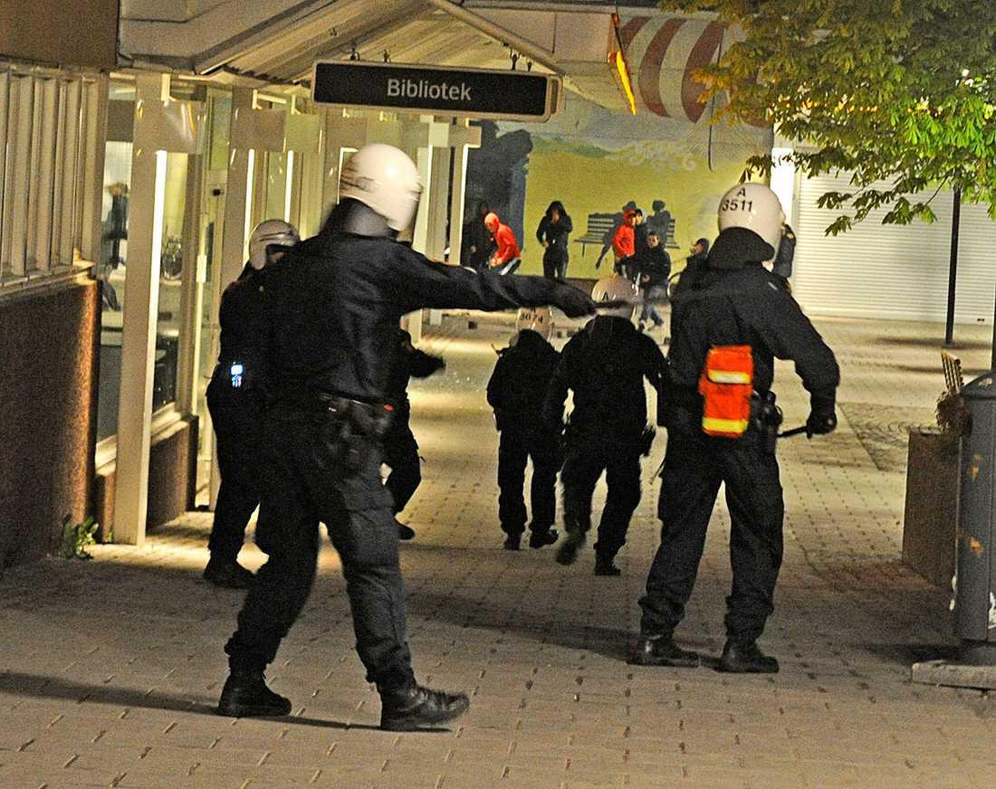 I förgrunden poliser med hjälmar och batonger. i Bakgrunden stenkastande ungdomar.