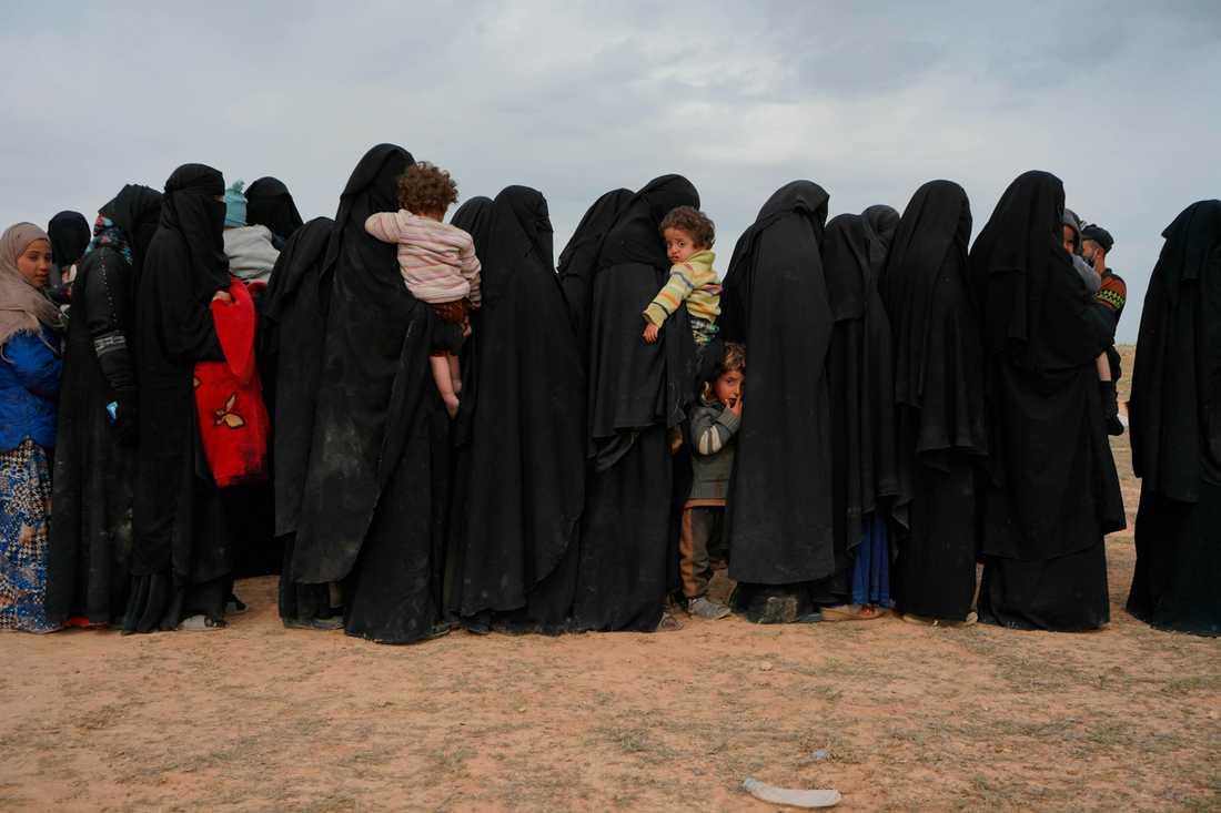 Kvinnor och barn väntar framför en kontroll vid samlingsplatsen för de människor som senast evakuerats ur IS sista fäste i Syrien.
