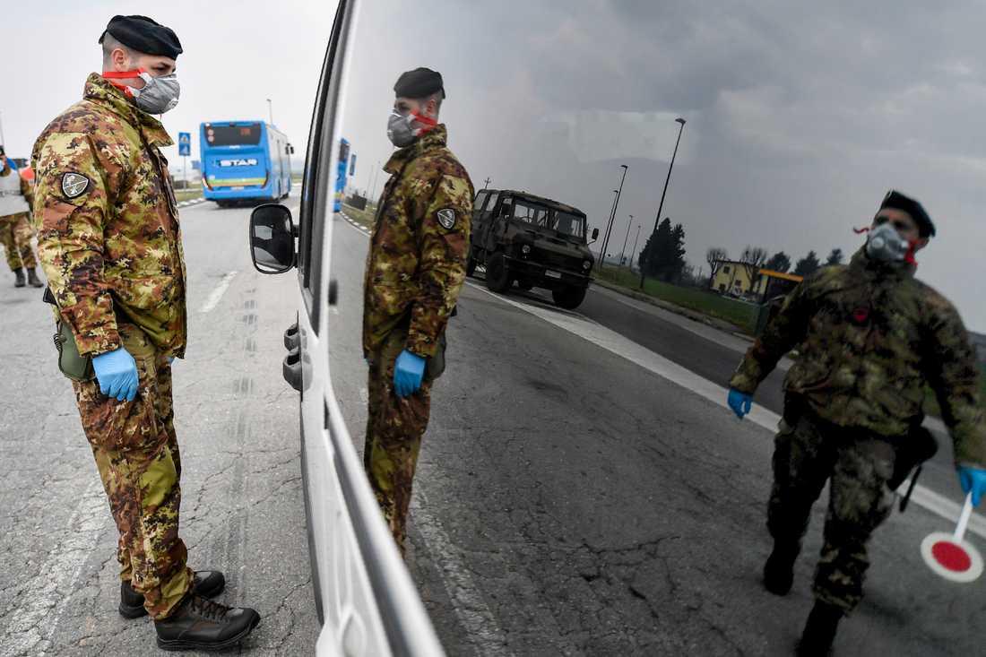 Italienska soldater kontrollerar fordon som vill passera vid de isolerade områdena i norra Italien.