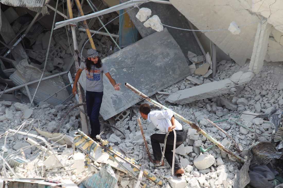 Män söker efter överlevande efter flygkraschen på en marknadsplats i nordvästra Syrien.