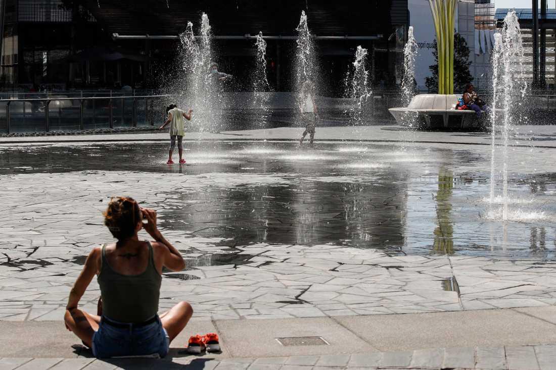 Barn svalkar sig i en fontän i Milano under värmeböljan.