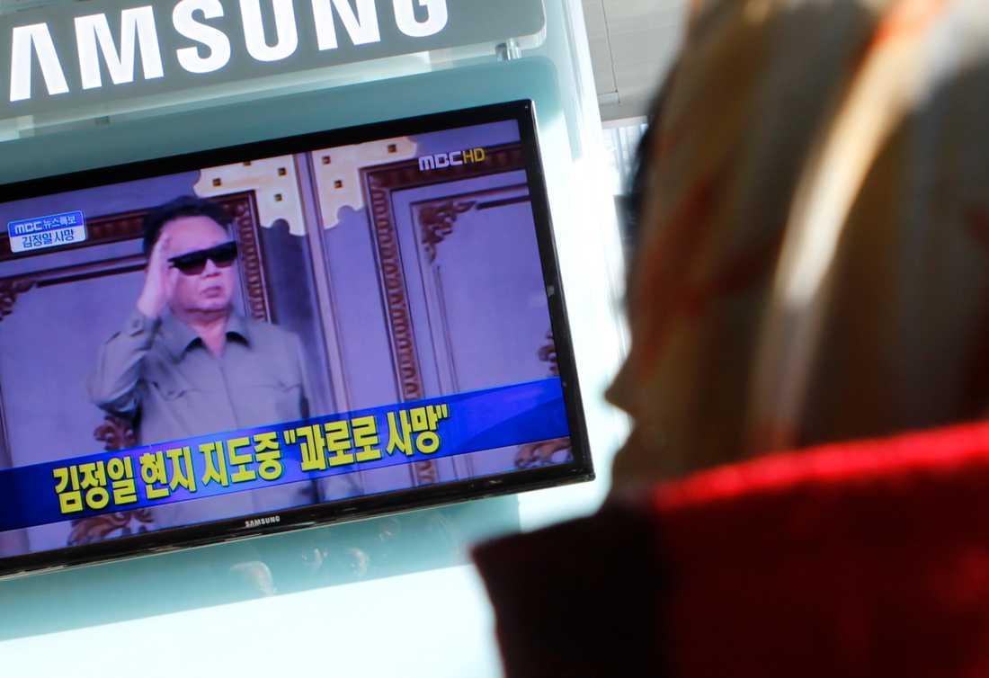 En kvinnan får beskedet att Kim Jong Il dött via tv:n.