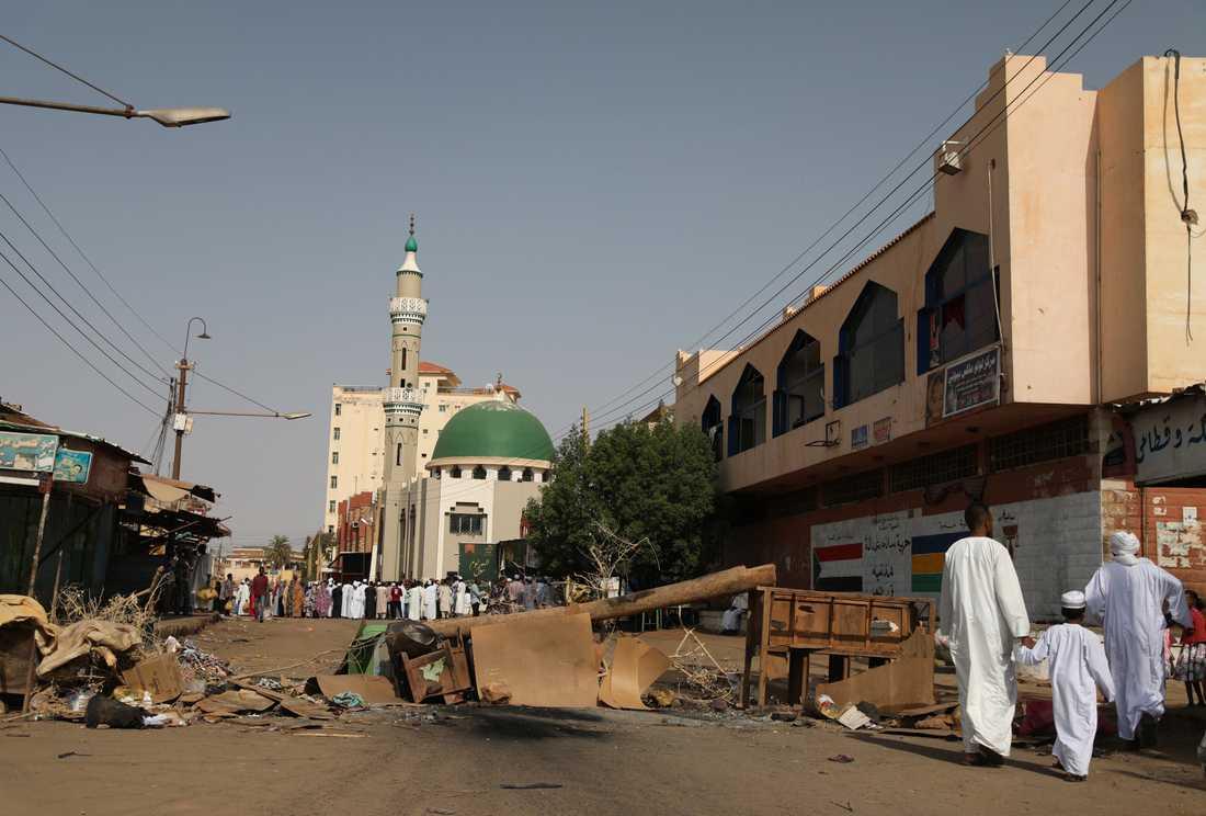 Vuxna och barn kryssar mellan barriärer uppsatta av demonstranter för att hindra militären från att ta sig in i på en av Khartums huvudgator.