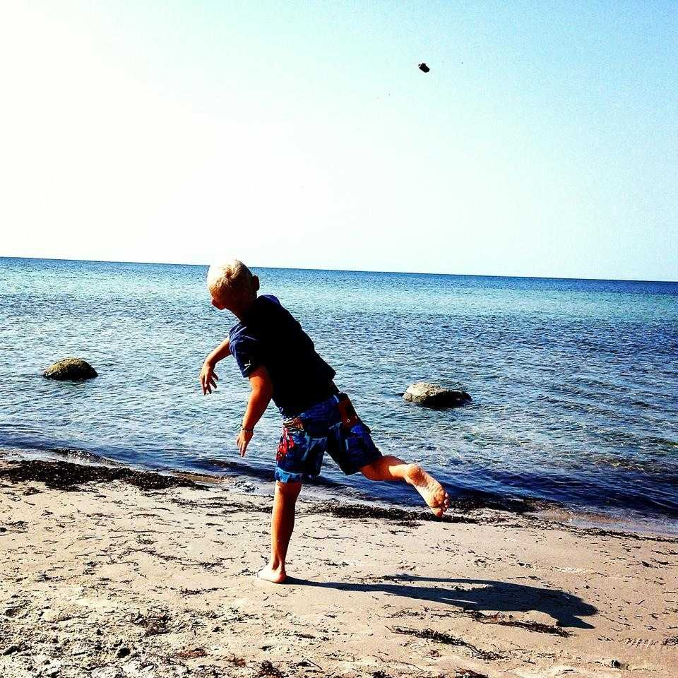 Min son Abbe kastar sten på stranden i Kämpinge