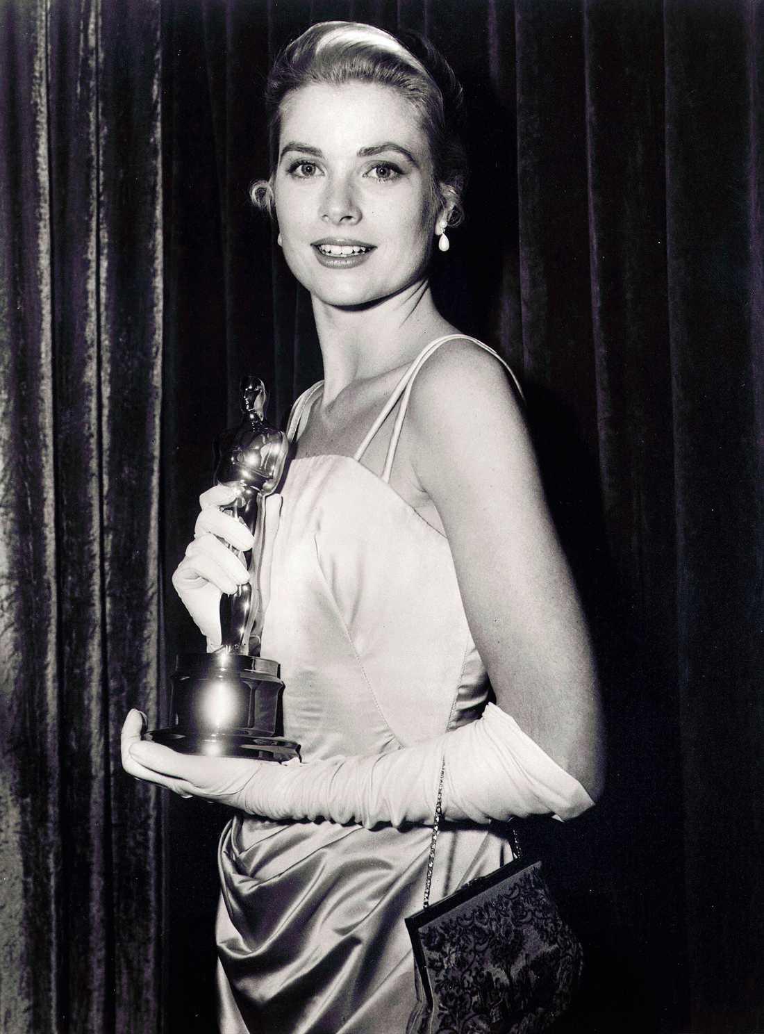 """Grace Kelly 1955 """"Precis som Audrey Hepburn var Grace Kelly mer än en larger than life-stjärna. Hon var en ikon, en idol, en blivande prinsessa. Kelly teamade upp med lika legendariska kostymdesignern Edith Heed som själv vunnit 8 (!!) Oscars för sina kostymer. Naturligtvis en klänning att minnas och säga aaaaaaaw till."""""""
