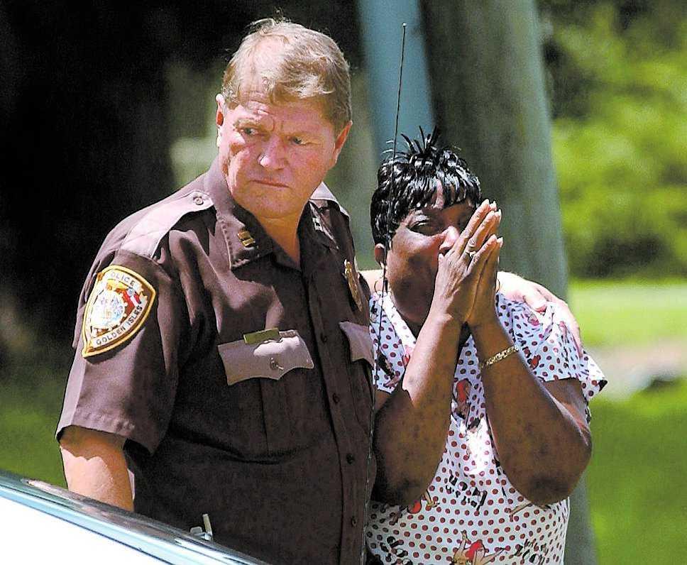 Poliskapten Jack Boyet tröstar en kvinna som skriker ut sin förtvivlan efter massmordet på campingen.