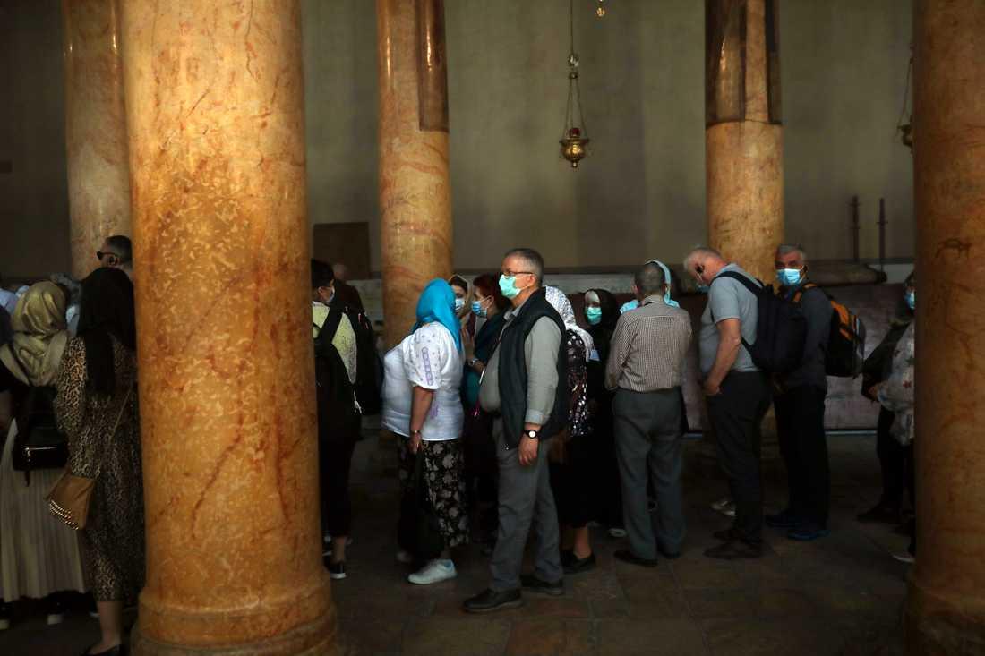 Människor besöker Födelsekyrkan i Betlehem. Nu stängs kyrkan på grund av coronaviruset under de kommande två veckorna.