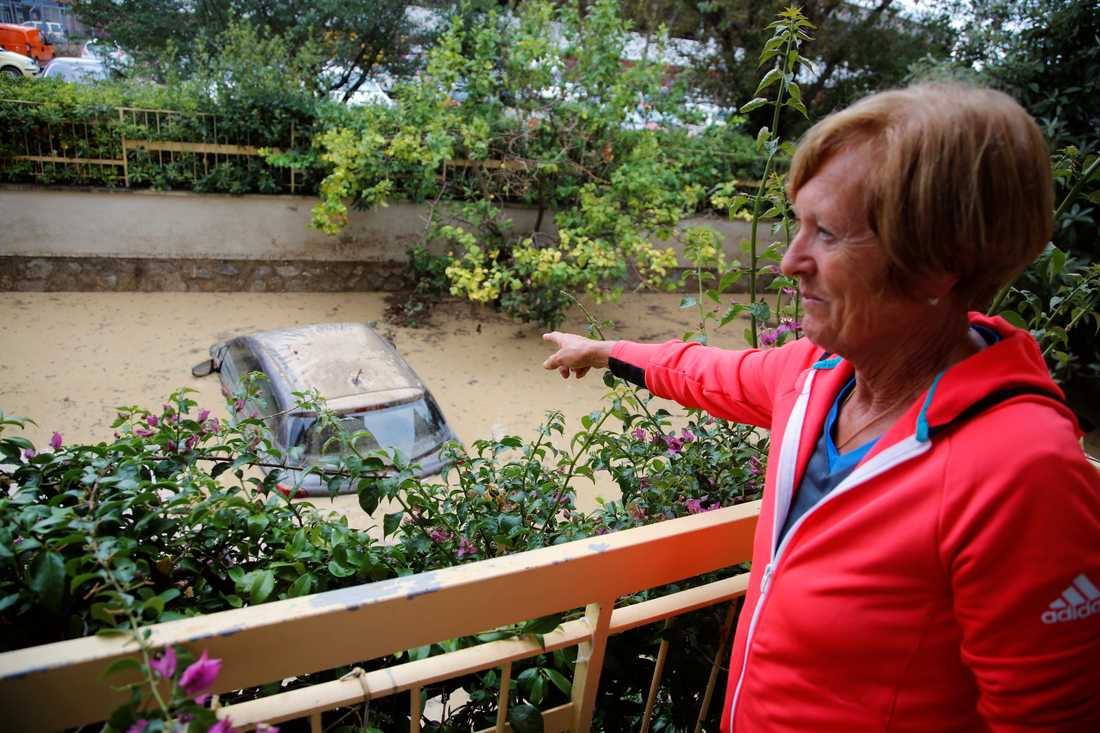 En kvinna pekar på sin bil utanför sitt hem. Översvämningarna i Italien har inte bara kostat liv, utan också orsakat stora materiala skador.