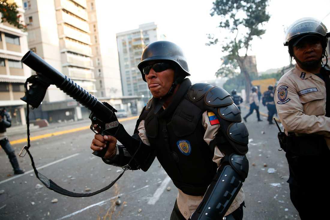 Kravallpolis skuter med tårgas mot demonstranterna.