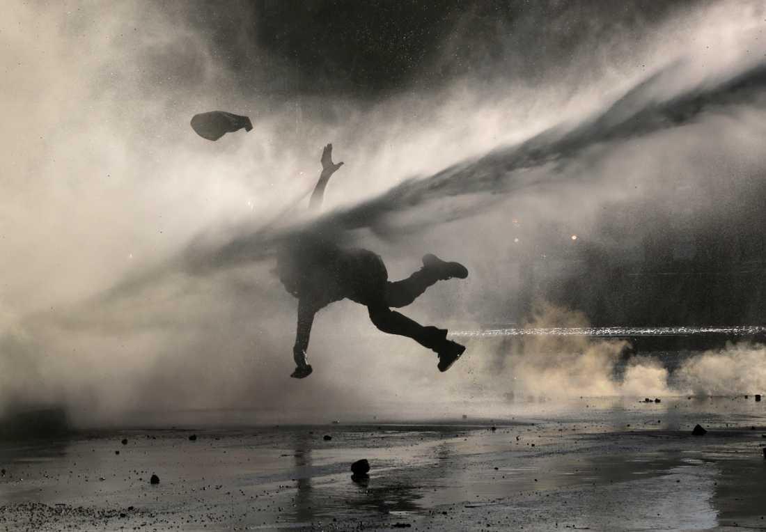 En demonstrant slungas i väg av en av polisens vattenkanoner under en demonstration i måndags.