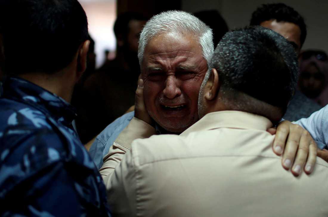 En släkting till en palestinsk man som dog i protesterna tröstas på sjukhus i Gaza.