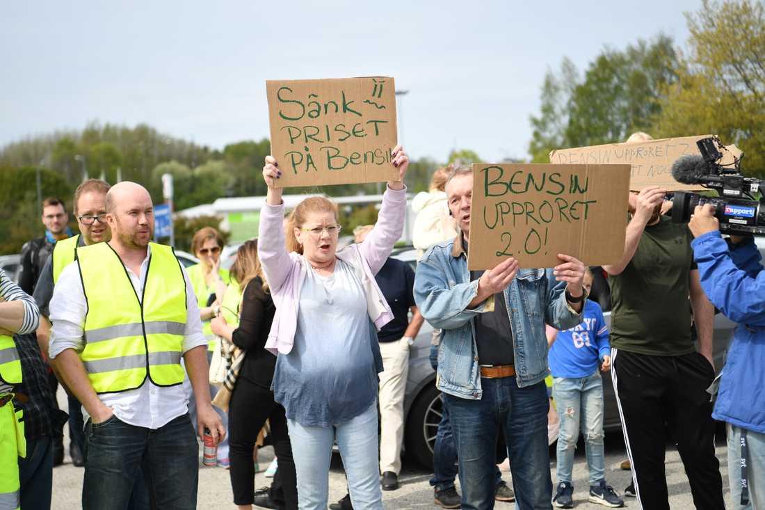 Ett hundratal, många i gula västar, mötte upp på en parkeringsplats i Barkarby norr om Stockholm för att protestera mot det allt högre bensinpriset.