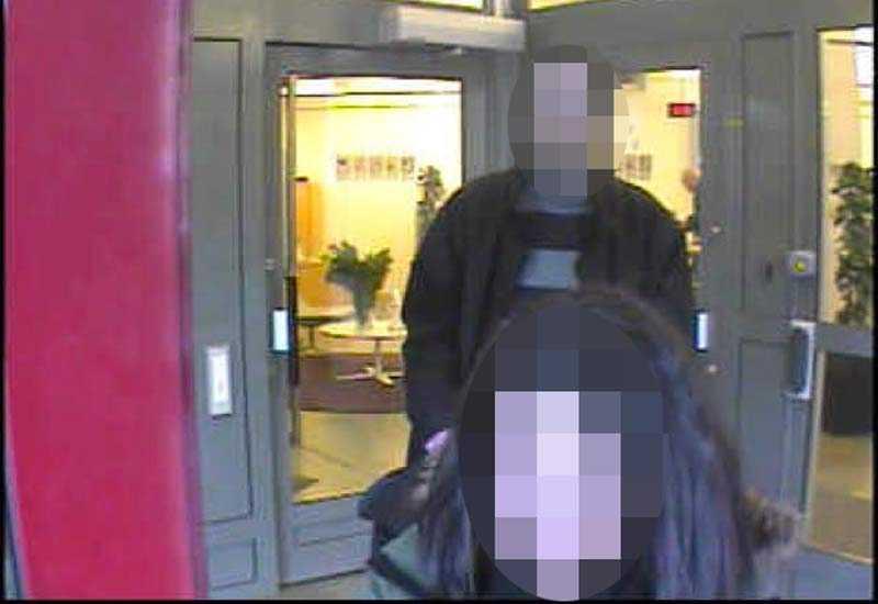 Den misstänkta kvinnan och en av de misstänkta männen kommer ut från ett bankkontor.