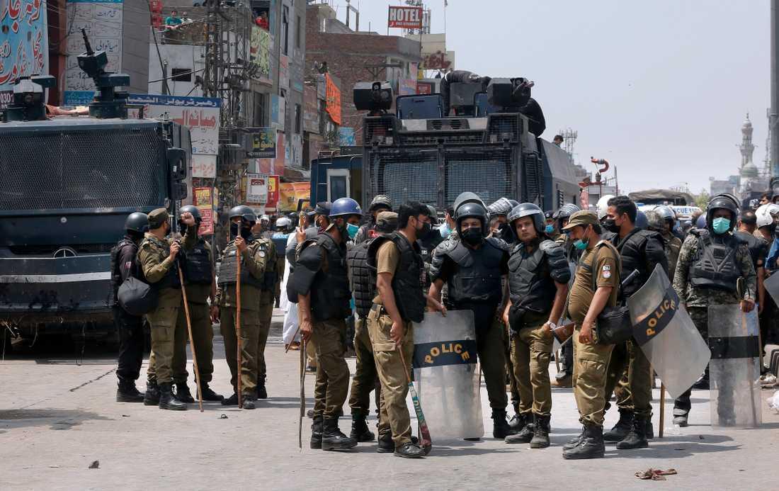 Poliser samlas efter sin insats vid de våldsamma protesterna i söndags i Lahore.