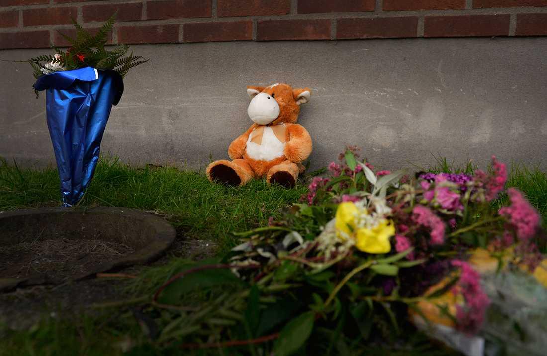 Blommor och nallar har lämnats av sörjande och boende utanför lägenheten där pojken dog.