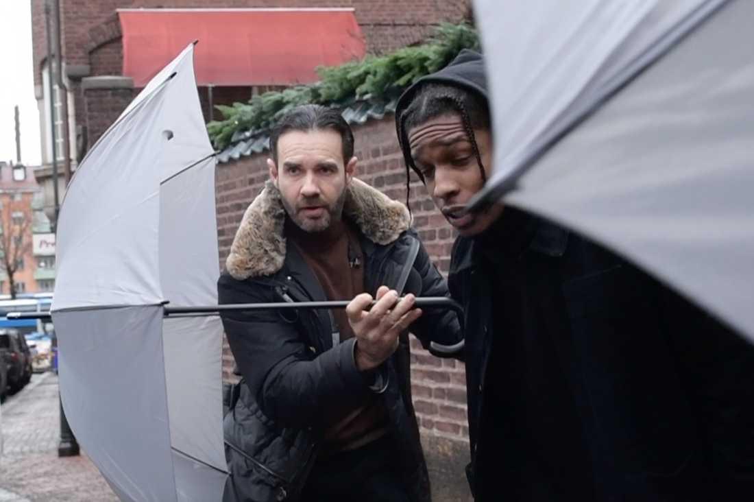 Asap Rocky är tillbaka i Stockholm vid lunchtid lämnade han lyxhotellet – skyddad av paraplyer.