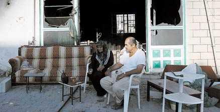Ett libanesiskt par framför sin förstörda affär i staden Khiam i södra Libanon.