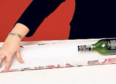 1. Mät ut ett papper på dubbla flaskans längd samt flaskans omkrets i bredd + 2 cm. Flaskan är hal, tejpa därför fast första papperskanten på flaskans glas (där det inte skadar etiketten). Om flaskan har en inbuktad botten, sätt tejpbitar i kors för en stabil bas.