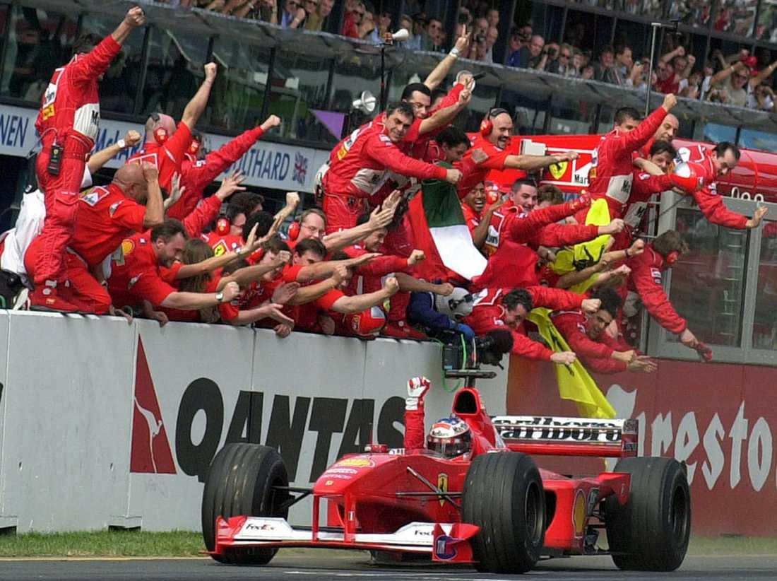 """2000 """"Schumi"""" firas av sitt (dåvarande) team i Ferrari när han kör mot mållinjen och segern i Australian Formel One Grand Prix."""
